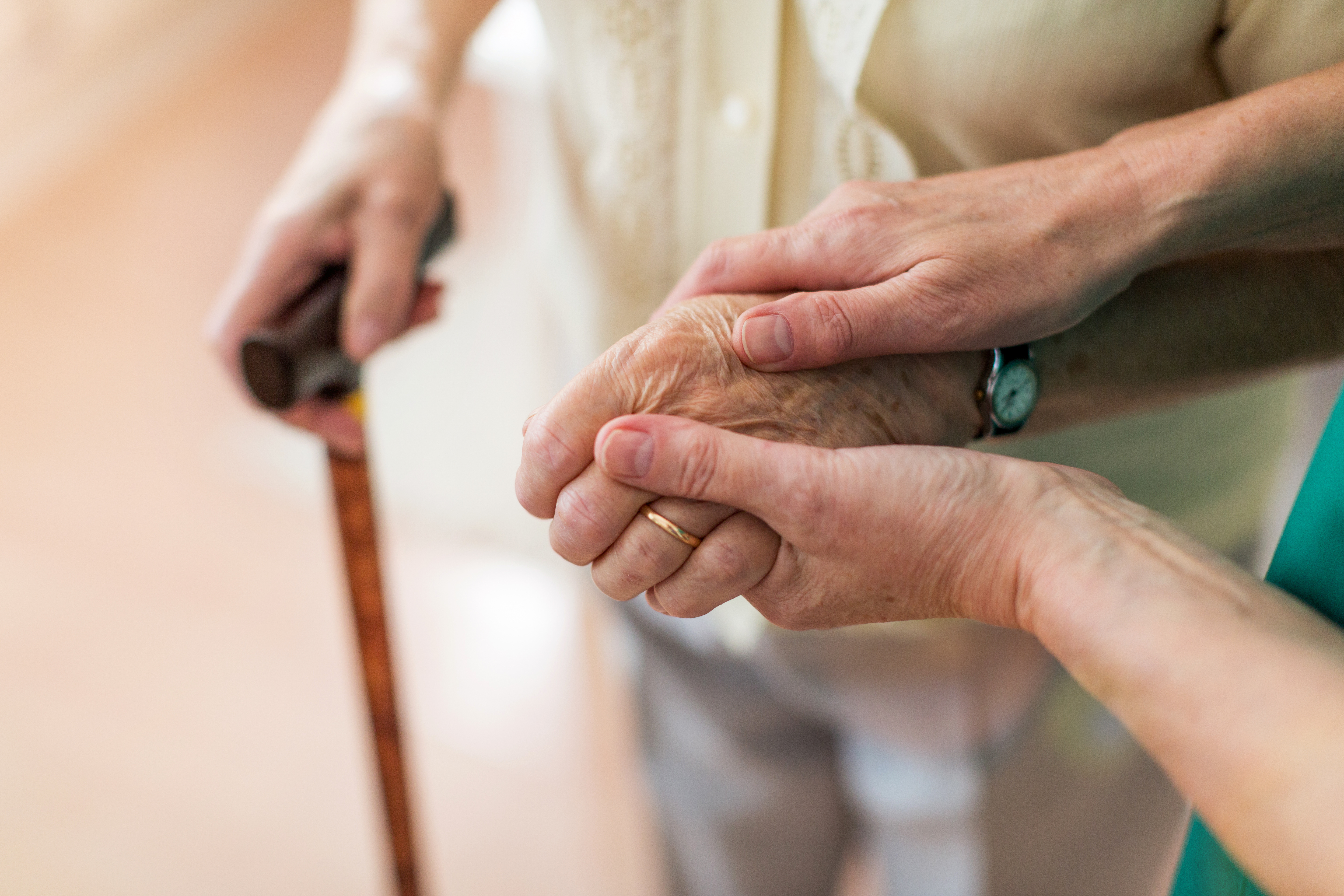Daughter helping her elderly dementia-diagnosed mother by holding her hands