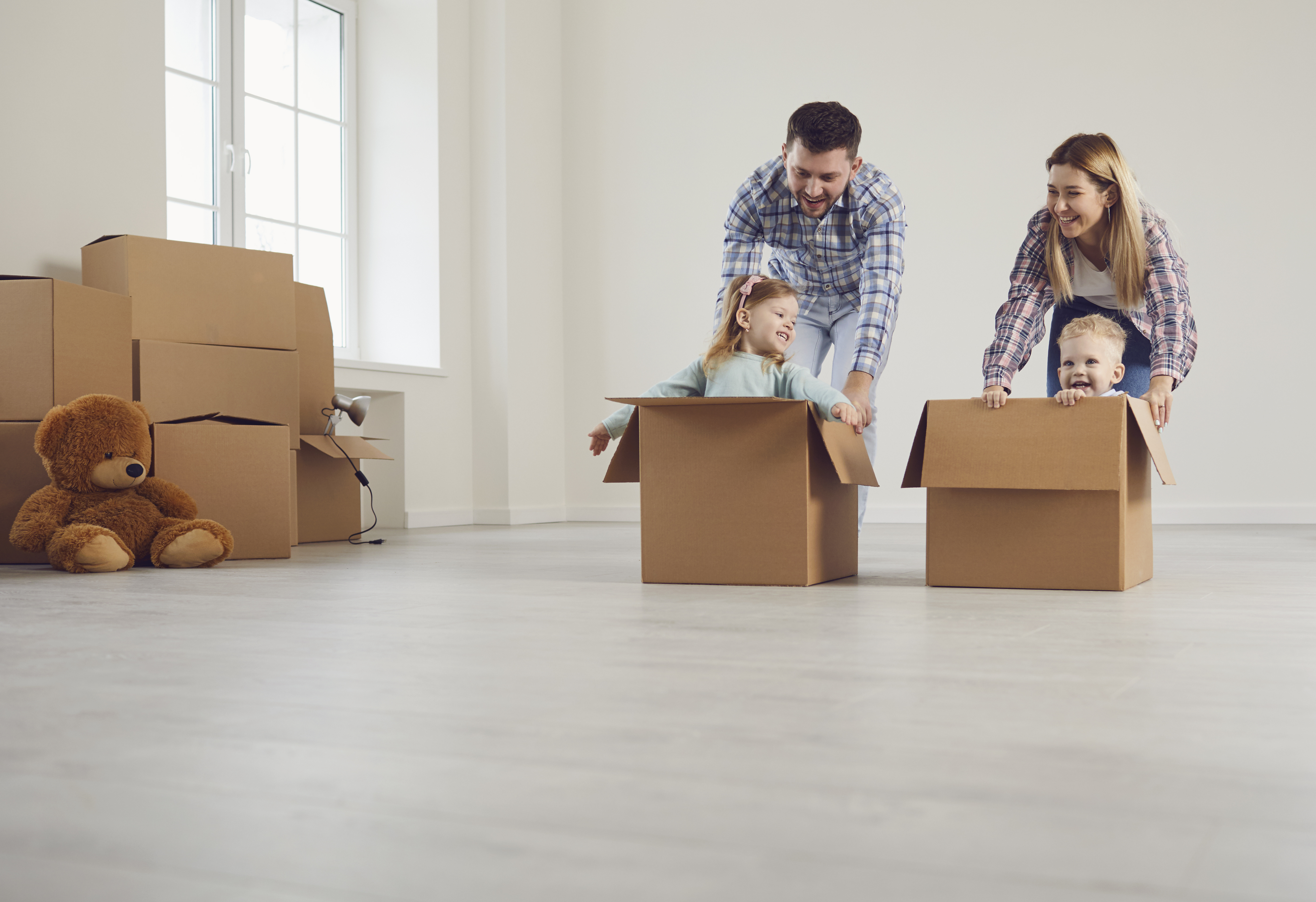 Happy family on life insurance have fun playing in a new house in the room.